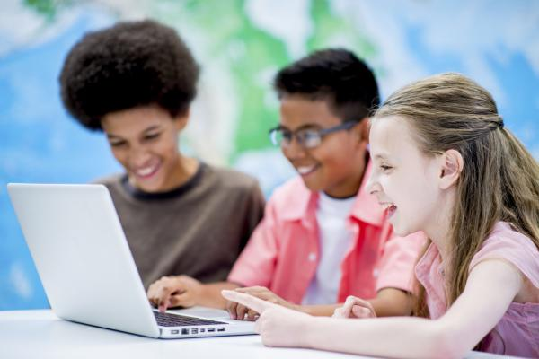 Two students sitting at a computer with teacher